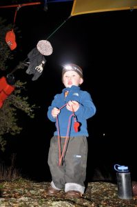 2-year-old Sam uses of his personal headlamp around camp. Photo: Rick Shone
