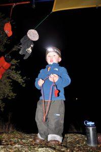 2-year-old Sam uses of his personal headlamp around camp. Photo: Rick Shone