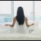 awoman-meditating-white-bed