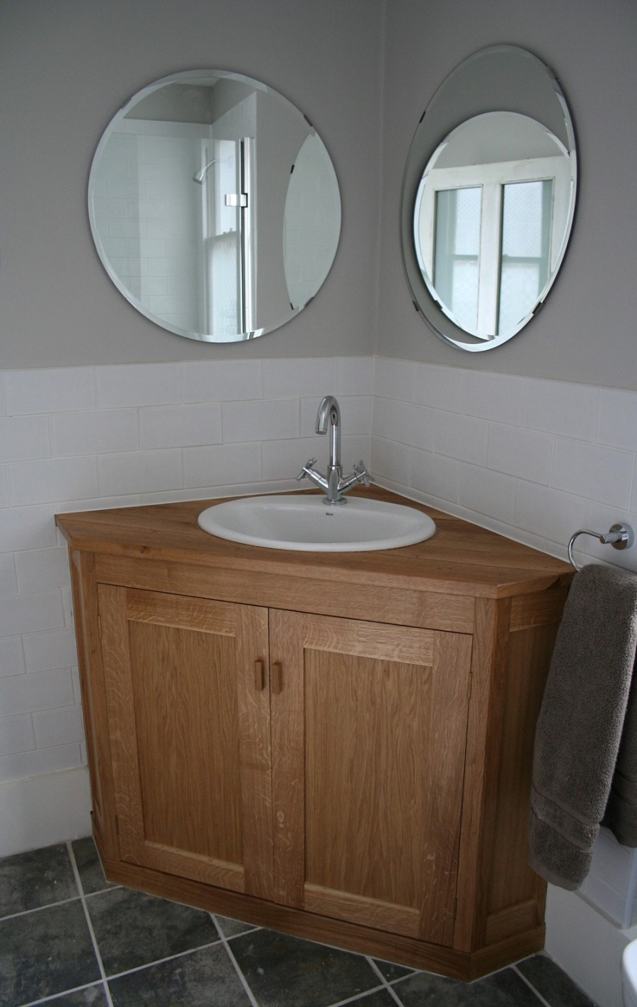 Fascinating Round Wall Mirrors Above Wooden Corner Bathroom Vanity With White Mounted Sink Marc And Mandy Show