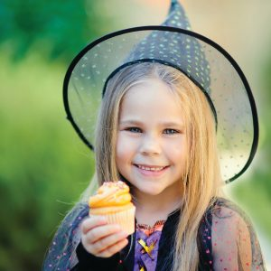 Happy Little girl wearing witch costume eat cupcake on Halloween