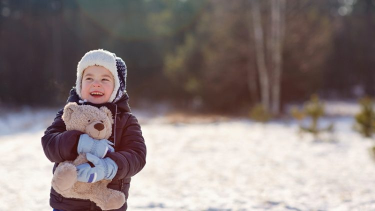 Adorable little boy holding his teddy bear outdoors on a snowy winter's day