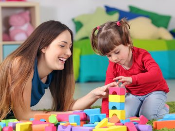 Mother and daughter playing with construction toys