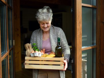 Front view portrait of woman holding food shopping delivery by front door.