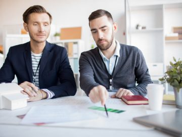 Portrait of real estate agent helping client choosing house in agency