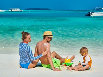 family-with-three-year-old-boy-on-beach-9SEARFB
