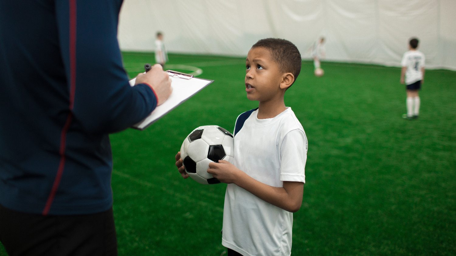 Adorable football player with ball talking to his trainer on pitch after game