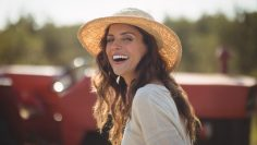 Portrait cheerful young woman wearing sun hat at farm